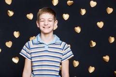 Αγόρι που γελά στο χρυσό υπόβαθρο καρδιών Στοκ εικόνα με δικαίωμα ελεύθερης χρήσης