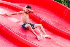 Αγόρι που γλιστρά σε μια φωτογραφική διαφάνεια νερού Στοκ Εικόνες
