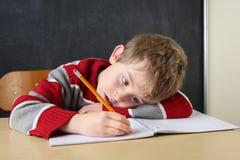 Αγόρι που γράφει στο γραφείο του Στοκ Φωτογραφία