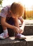 Αγόρι που δένει τις δαντέλλες στα πάνινα παπούτσια ο ίδιος Στοκ φωτογραφία με δικαίωμα ελεύθερης χρήσης