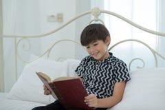 Αγόρι που διαβάζει ένα βιβλίο, χαμόγελο, ευτυχές στο κρεβάτι η εκπαίδευση έννοιας βιβλίων απομόνωσε παλαιό Στοκ Φωτογραφίες