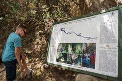 Αγόρι που διαβάζει τον πίνακα πληροφοριών για την άνοιξη - πηγή νερού, Oliena, Nuoro, Σαρδηνία, Ιταλία στοκ φωτογραφίες