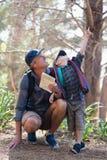 Αγόρι που δείχνει ενώ άτομο που ανατρέχει στο δάσος Στοκ εικόνες με δικαίωμα ελεύθερης χρήσης