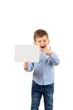 Αγόρι που δείχνει στην άσπρη κενή κάρτα Στοκ εικόνα με δικαίωμα ελεύθερης χρήσης