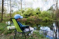 Αγόρι που εγκαθιστά με τη ράβδο κοντά στη μικρή λίμνη Αλιεία παιδιών στοκ φωτογραφία με δικαίωμα ελεύθερης χρήσης