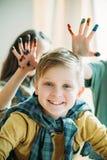 Αγόρι που εξετάζει τη κάμερα, κορίτσια με τα χρωματισμένα χέρια πίσω παιδιά που σύρουν τη σχολική έννοια στοκ φωτογραφίες με δικαίωμα ελεύθερης χρήσης