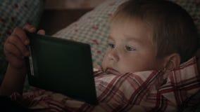 Αγόρι που εξετάζει τον υπολογιστή ταμπλετών τη νύχτα απόθεμα βίντεο
