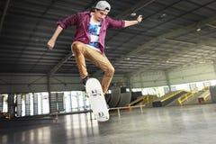 Αγόρι που κάνει σκέιτ μπορντ την έννοια Hipster τρόπου ζωής άλματος Στοκ Φωτογραφίες