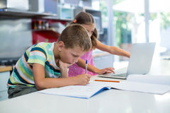Αγόρι που κάνει την εργασία του ενώ κορίτσι που χρησιμοποιεί το lap-top στην κουζίνα Στοκ Φωτογραφίες