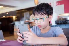 Αγόρι που κάνει την πίεση προσώπου παίζοντας τα παιχνίδια στο κύτταρο pH Στοκ Εικόνες