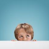 Αγόρι που κρυφοκοιτάζει πέρα από έναν λευκό πίνακα Στοκ Φωτογραφίες