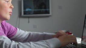 Αγόρι που μελετά στην κρεβατοκάμαρα που χρησιμοποιεί το lap-top απόθεμα βίντεο