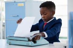 Αγόρι που μιμείται ως επιχειρηματία το έγγραφο ρύθμισης για τη γραφομηχανή Στοκ φωτογραφία με δικαίωμα ελεύθερης χρήσης