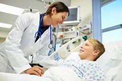 Αγόρι που μιλά στο θηλυκό γιατρό στη εντατική Στοκ Εικόνες