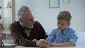 Αγόρι που νικά εύκολα τον παππού στην πάλη βραχιόνων ευτυχή με τη νίκη, οικογενειακή διασκέδαση απόθεμα βίντεο