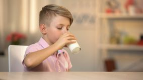 Αγόρι που πίνει το φρέσκο οργανικό γάλα από το γυαλί στον πίνακα, ενεργειακά τρόφιμα πρωινού, γαλακτοκομείο απόθεμα βίντεο