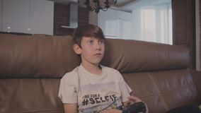 Αγόρι που παίζει τα τηλεοπτικά παιχνίδια στην κονσόλα ο επάνω καναπές στο σπίτι απόθεμα βίντεο
