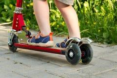 Αγόρι που παίζει το μίνι μηχανικό δίκυκλο, μηχανικό δίκυκλο λακτίσματος στο πάρκο Στοκ Φωτογραφία