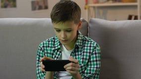 Αγόρι που παίζει το τηλεοπτικό παιχνίδι στο smartphone στο σπίτι, εθισμός σ απόθεμα βίντεο