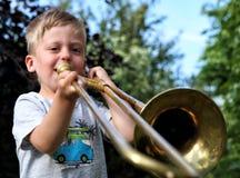 Αγόρι που παίζει το χρυσό τρομπόνι υπαίθρια Στοκ εικόνες με δικαίωμα ελεύθερης χρήσης