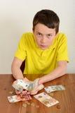 Αγόρι που παρουσιάζει υπερήφανα χρήματά του Στοκ Φωτογραφία