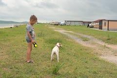 Αγόρι που περπατά με ένα σκυλί σε έναν πράσινο χορτοτάπητα Στοκ φωτογραφία με δικαίωμα ελεύθερης χρήσης