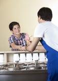 Αγόρι που πληρώνει για το παγωτό φραουλών στο σερβιτόρο στην αίθουσα στοκ εικόνα με δικαίωμα ελεύθερης χρήσης