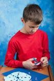 Αγόρι που ρόδινο snowflake εγγράφου με το ψαλίδι Στοκ Φωτογραφία