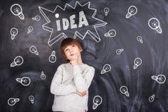 Αγόρι που σκέφτεται και στο υπόβαθρο στον πίνακα κιμωλίας που χρωματίζεται lig Στοκ εικόνες με δικαίωμα ελεύθερης χρήσης