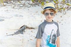 Αγόρι που στέκεται στο υπόβαθρο άμμου με το iguana στοκ φωτογραφία