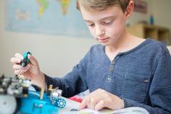 Αγόρι που συγκεντρώνει τη ρομποτική εξάρτηση στην κρεβατοκάμαρα στοκ φωτογραφίες