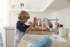 Αγόρι που συμπιέζει πλένοντας επάνω το υγρό στο νεροχύτη για να πλύνει τα πιάτα Στοκ Εικόνες
