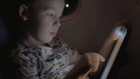 Αγόρι που ταξιδεύει με το αεροπλάνο και το παίζοντας παιχνίδι στο PC ταμπλετών απόθεμα βίντεο