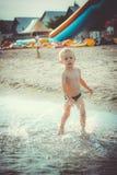 Αγόρι που τρέχει κατά μήκος του νερού στην παραλία Στοκ Εικόνες