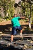 Αγόρι που τρέχει πέρα από τα ελαστικά αυτοκινήτου κατά τη διάρκεια της κατάρτισης σειράς μαθημάτων εμποδίων Στοκ φωτογραφία με δικαίωμα ελεύθερης χρήσης