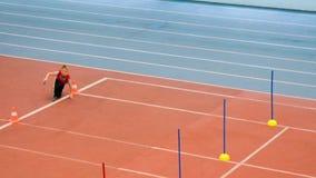 Αγόρι που τρέχει στον ηλεκτρονόμο στους ανταγωνισμούς αθλητισμού απόθεμα βίντεο