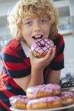 Αγόρι που τρώει παγωμένο doughnut στην κουζίνα Στοκ φωτογραφία με δικαίωμα ελεύθερης χρήσης