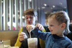 Αγόρι που τρώει τον αφρό του milkshake Στοκ Φωτογραφίες