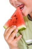 αγόρι που τρώει το καρπούζι φετών Στοκ Φωτογραφίες
