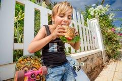 αγόρι που τρώει το χάμπουρ& Στοκ Φωτογραφίες
