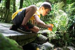 Αγόρι που φθάνει στο ρεύμα για το δροσερό καθαρό γλυκό νερό ποτών από το β Στοκ φωτογραφία με δικαίωμα ελεύθερης χρήσης
