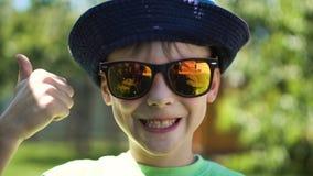 Αγόρι που φορά τα γυαλιά ηλίου και απόθεμα βίντεο