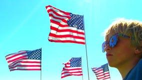 Αγόρι που φορά τα γυαλιά ηλίου που προσέχουν το κύμα αμερικανικών σημαιών στον αέρα απόθεμα βίντεο