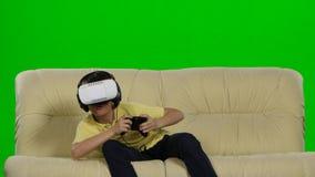 Αγόρι που φορά τα προστατευτικά δίοπτρα εικονικής πραγματικότητας Στούντιο πυροβοληθε'ν, άσπρος καναπές Πράσινος φιλμ μικρού μήκους
