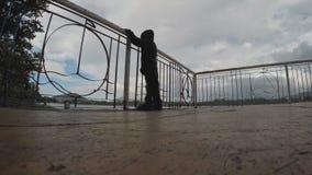 Αγόρι που φορά το παιχνίδι σακακιών κουκουλών στα κιγκλιδώματα λιμνών Σκιαγραφίες απόθεμα βίντεο