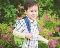 Αγόρι που χαμογελά με το σακίδιο πλάτης που αντιμετωπίζει τη κάμερα που κρατά ένα λουλούδι στοκ φωτογραφία με δικαίωμα ελεύθερης χρήσης