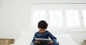 Αγόρι που χρησιμοποιεί την ψηφιακή ταμπλέτα χαλαρώνοντας στο κρεβάτι φιλμ μικρού μήκους