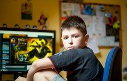Αγόρι που χρησιμοποιεί τον υπολογιστή στο σπίτι, που παίζει το παιχνίδι Στοκ φωτογραφίες με δικαίωμα ελεύθερης χρήσης