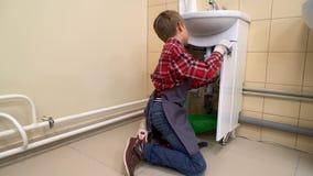 Αγόρι που χρησιμοποιεί το κατσαβίδι για να καθορίσει το νεροχύτη απόθεμα βίντεο