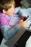Αγόρι που χρησιμοποιεί το κινητό τηλέφωνο αντί της μελέτης στην κρεβατοκάμαρα Στοκ φωτογραφία με δικαίωμα ελεύθερης χρήσης